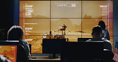 Medium long shot of technicians walking around in control room while Mars Rover moving on digital screen