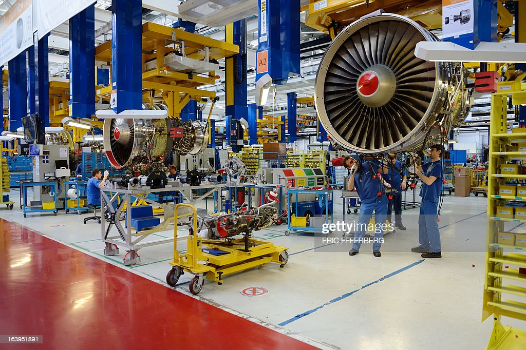 Technicians work at the assembly line for jet engines of French aerospace and defence group Safran, manufacturing engines for commercial and military aircraft, on March 18, 2013 at the SNECMA Villaroche site in Moissy-Cramayel, south east of Paris. AFP PHOTO ERIC FEFERBERG