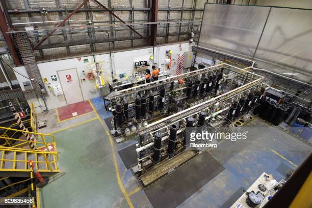 Technicians work behind equipment at a Rio Tinto Group research laboratory in Melbourne Australia on Friday Aug 11 2017 Tests at a research facility...