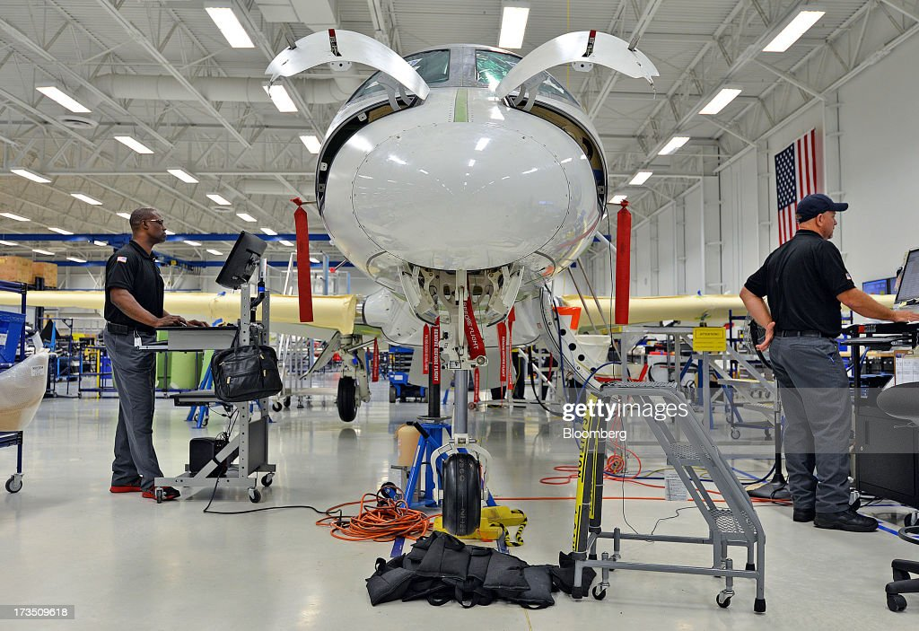 Technicians work on an Embraer SA Phenom 300 Light business jet at the company's executive jet manufacturing facility in Melbourne, Florida, U.S., on Monday, July 15, 2013. Embraer SA, the world's largest manufacturer of commercial jets up to 120 seats, delivered 22 jets to the commercial aviation market and 29 to the executive aviation market, for a total of 51 aircraft in the second quarter of 2013, according to a company press release. Photographer: Mark Elias/Bloomberg via Getty Images