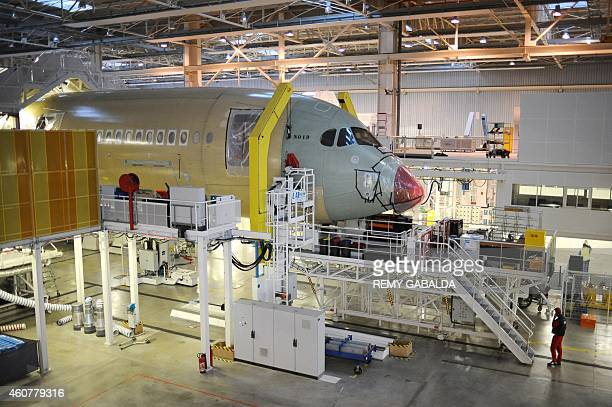 Technicians work on the assembly line of an Airbus A350 at the Airbus headquarters in Toulouse on December 22 2014 Airbus delivered its first...