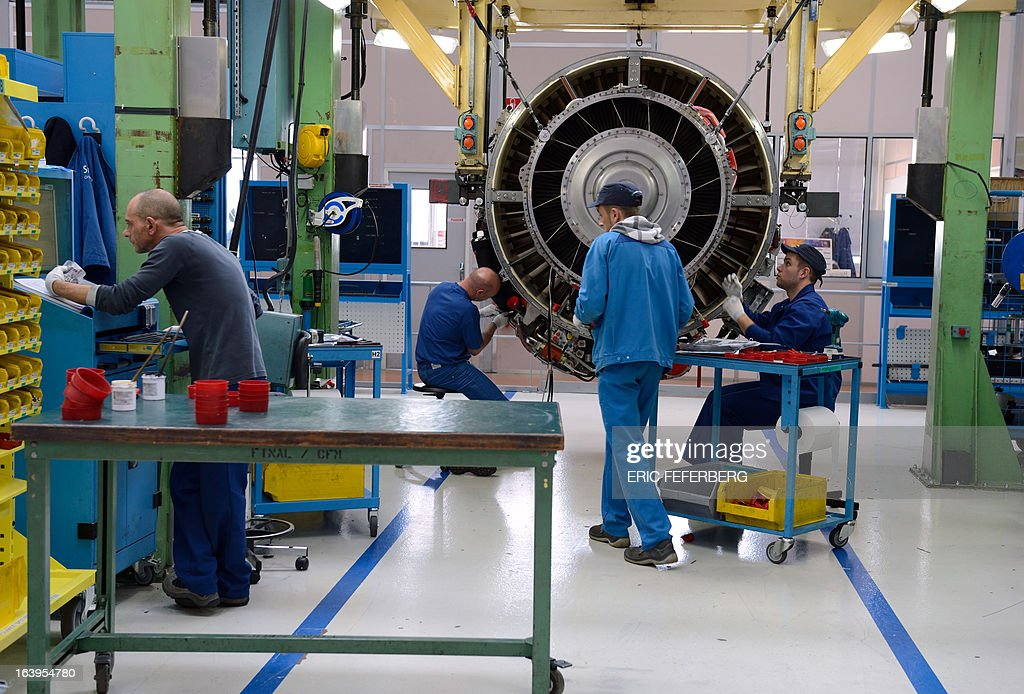 Technicians work on the assembly line of French aerospace and defence group Safran putting together SECMA-SAFRAN CFM 56 jet engines for commercial and military aircraft, on March 18, 2013 at the SNECMA Villaroche site in Moissy-Cramayel, south east of Paris.