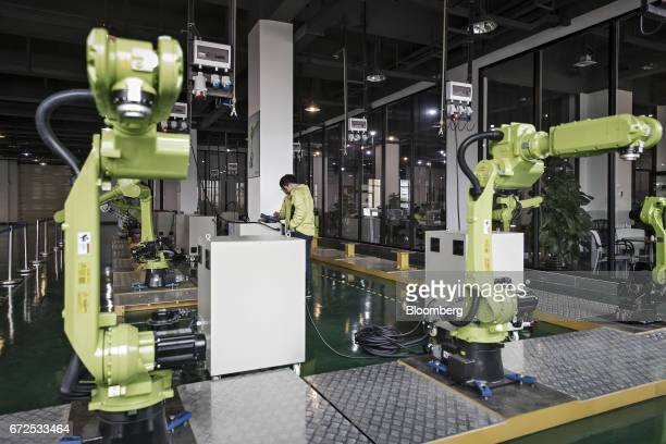 Technicians work on the testing line of a factory operated by EDeodar Robot Equipment Co a whollyowned subsidiary of Ningbo Techmation Co in Foshan...