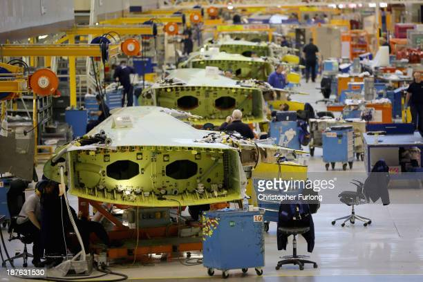 Technicians work on the wing of an Airbus A320 during construction at the Airbus SAS factory on November 7 2013 in Broughton United Kingdom The...
