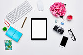 Directly above shot of technologies and office supplies. Digital tablet is surrounded by equipment and hydrangea. All are on white bloggers desk.