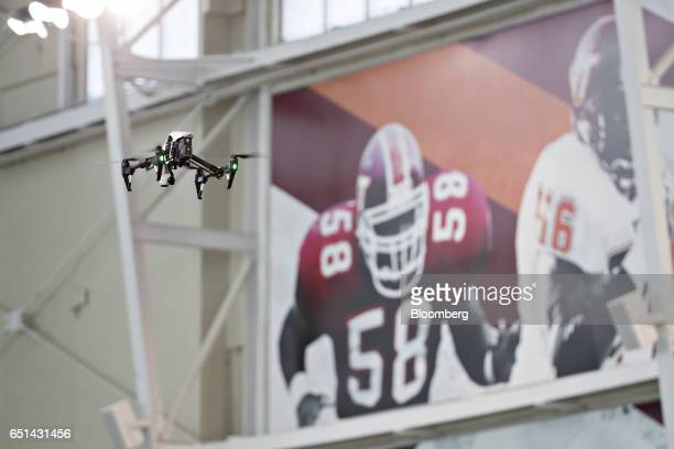 Technology Co Inspire 1 drone flies in front of posters before test experiments are performed with unmanned aerial systems on the campus of Virginia...