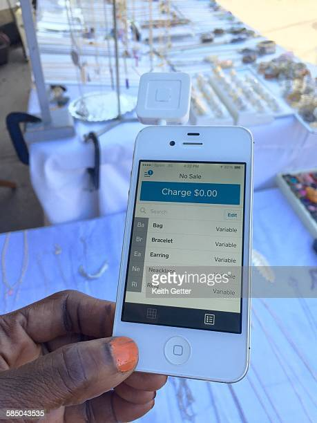 A jewelry vendor at an outdoors craft market holds her credit card reader attached to a smart device for mobile point of sales activity