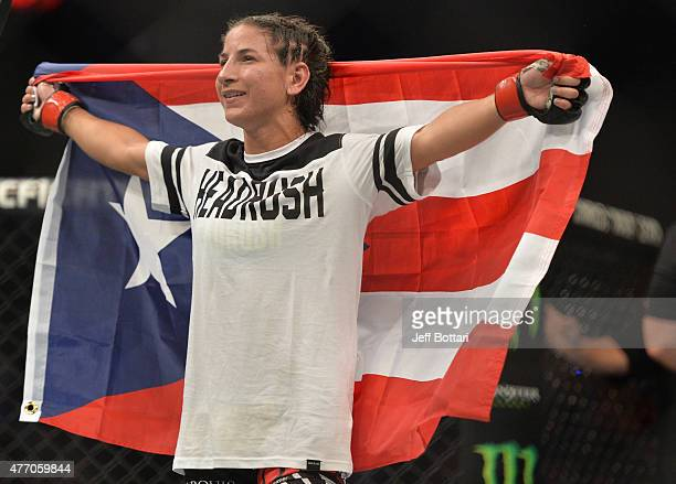 Tecia Torres of the United States celebrates her victory over Angela Hill of the United States in their women's strawweight bout during the UFC 188...