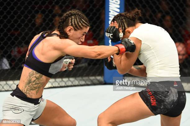 Tecia Torres punches Michelle Waterson in their women's strawweight bout during the UFC 218 event inside Little Caesars Arena on December 02 2017 in...