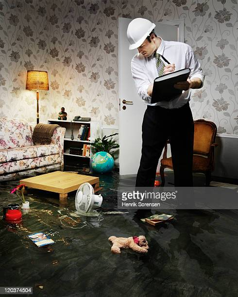 tecnician checking damage in flooded room