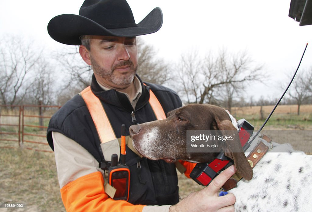 Ted Gartner checks the GPS collar on Vegas, one of his hunting dogs, December 19, 2012, in Edwards County, Kansas.