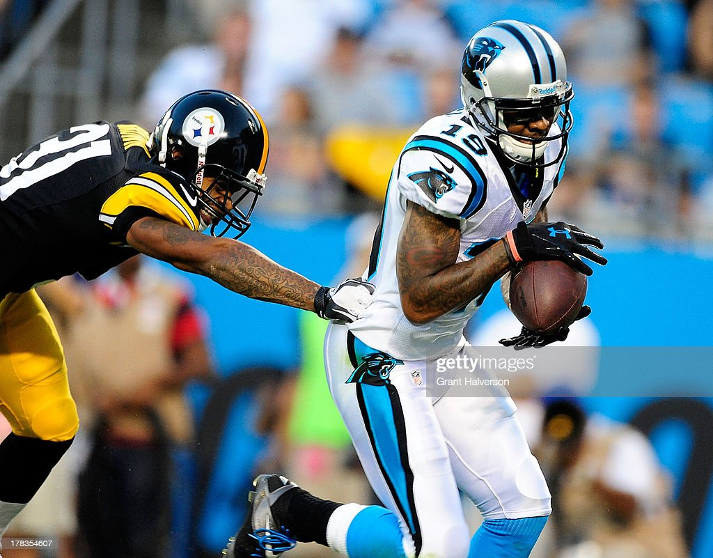 Ted Ginn Jr. #19 of the Carolina Panthers hangs on to the ball for a touchdown catch against Curtis Brown #31 of the Pittsburgh Steelers during a preseason NFL game at Bank of America Stadium on August 29, 2013 in Charlotte, North Carolina.