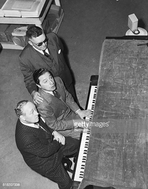 Ted Koehler lyricist and Harold Arlen song composer sing 'After All' their new song for blind J Robert Atkinson manager of the Braille Institute in...