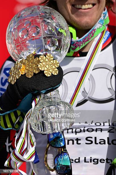 Ted Ligety of the US smiles as he poses with his trophy and his gold medals collected at the last World Championships after winning the Men's Giant...