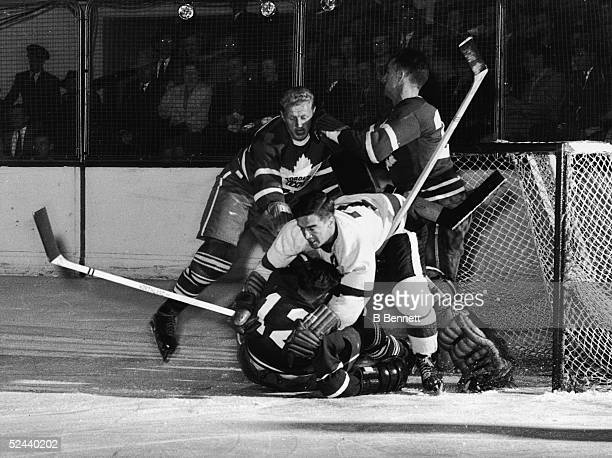 Ted Lindsay of the Detroit Red Wings collides with Fern Flaman of the Toronto Maple Leafs while Leafs goalkeeper Al Rollins tries to keep an eye on...