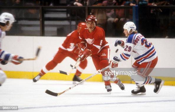 Ted Nolan of the Detroit Red Wings follows the play as Reijo Ruotsalainen of the New York Rangers defends during an NHL game circa November 1983 at...