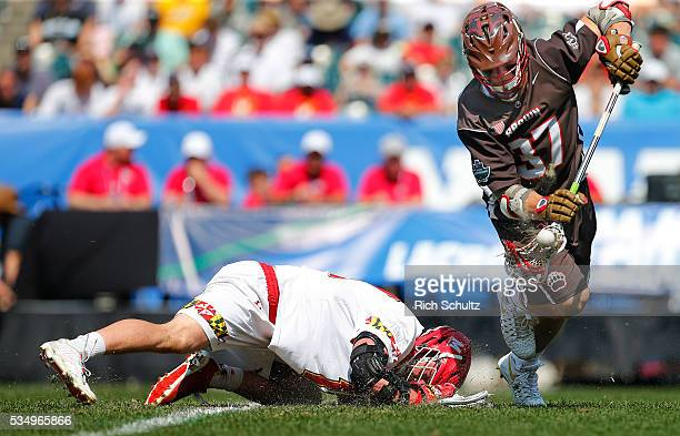 Ted Ottens of the Brown Bears controls the ball off the faceoff from Austin Henningsen of the Maryland Terrapins in the first quarter during a semi...