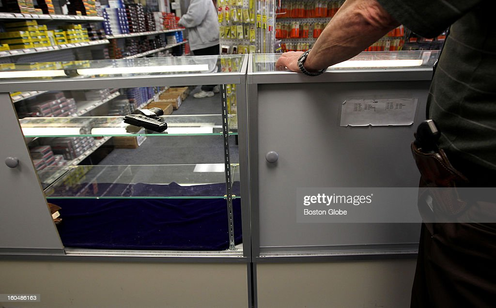 Ted Oven, right, owner of Northeast Trading Co., Inc. has had a hard time keeping guns in stock because of the skyrocketing demand. A lone Smith & Wesson M&P hand gun sits on a shelf in a case, awaiting a buyer.