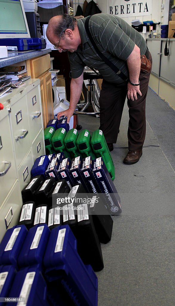 Ted Oven, right, owner of Northeast Trading Co., Inc., has had a hard time keeping guns in stock because of the skyrocketing demand. Ted, looks over brand new inventory that arrived in store. Some of the guns sold without ever being placed on store's shelves.