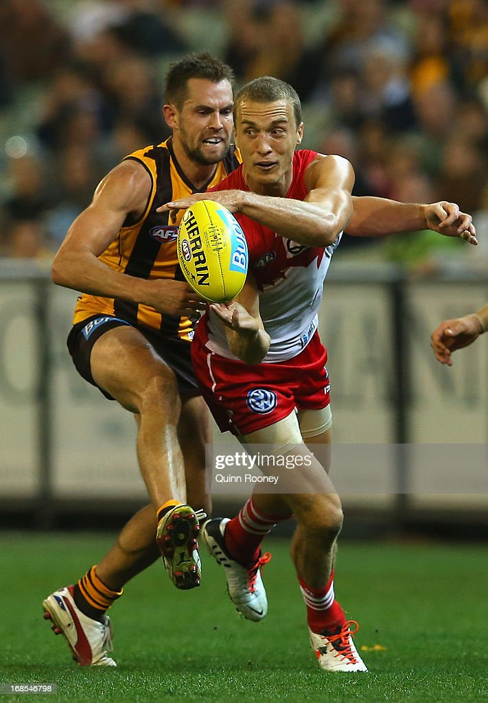 Ted Richards of the Swans handballs whilst being tackled by <a gi-track='captionPersonalityLinkClicked' href=/galleries/search?phrase=Luke+Hodge&family=editorial&specificpeople=241521 ng-click='$event.stopPropagation()'>Luke Hodge</a> of the Hawks during the round seven AFL match between the Hawthorn Hawks and the Sydney Swans at Melbourne Cricket Ground on May 11, 2013 in Melbourne, Australia.