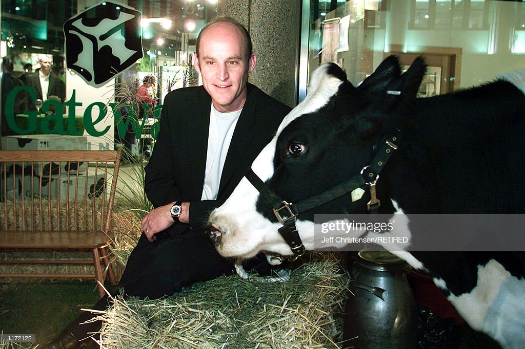 Ted Waitt, CEO of Gateway Computers sits with a cow outside of the Gateway country store October 24, 2001 in New York. Waitt was at the store to celebrate the retail availability of Microsoft's Windows XP operating system. The black and white cow markings are used in Gateway's logo and boxes.
