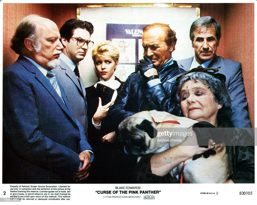 Ted Wass and Robert Loggia in crowded elevator with dog in a scene from the film 'Curse Of The Pink Panther' 1983