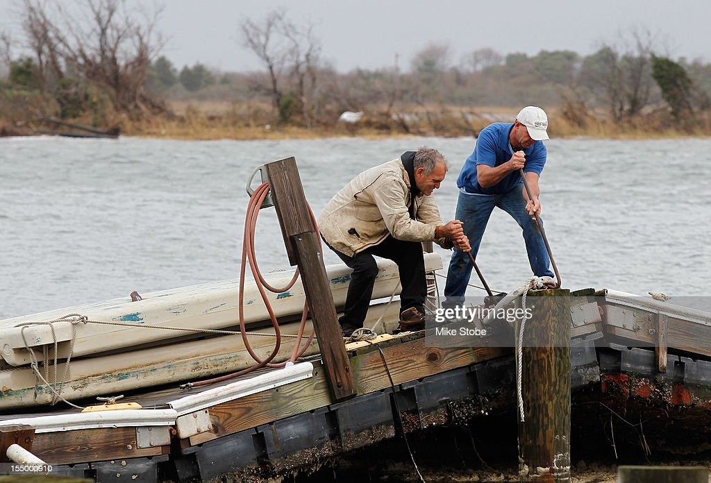 Ted Wondsel of Point Lookout (L), owner of Ted's Fishing Station, and a co-worker work on a sections of an old dock destroyed by flooding from Hurricane Sandy on October 30, 2012 in Long Beach, New York. The storm has claimed at least 33 lives in the United States, and has caused massive flooding across much of the Atlantic seaboard. U.S. President Barack Obama has declared the situation a 'major disaster' for large areas of the U.S. east coast, including New York City, with widespread power outages and significant flooding in parts of the city.