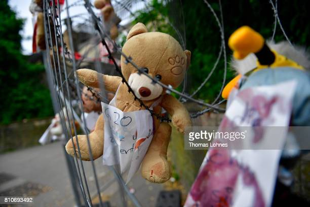 A teddy bear and other stuffed animals left by activists and some covered in ketchup hang fixed to the barbed wire security fencing around the...