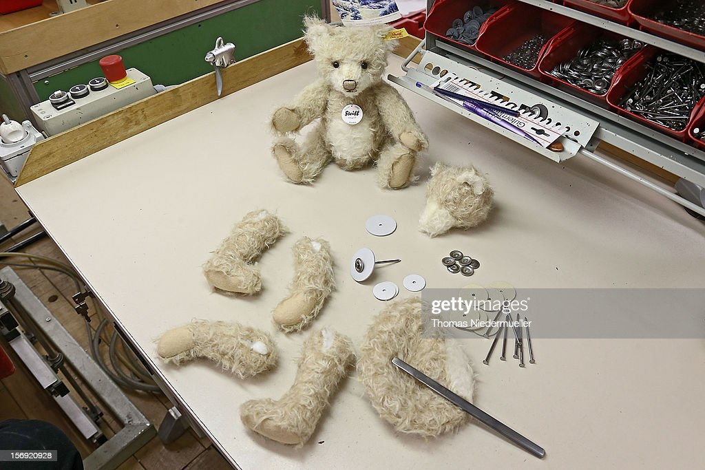 A teddy bear and the limbs and torso of an unassembled bear sit on a table at the Steiff stuffed toy factory on November 23 2012 in Giengen an der...