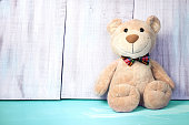 Teddy bear male sitting on blue floor on wooden background empty space for text.Toy birthday card.Childish concept.