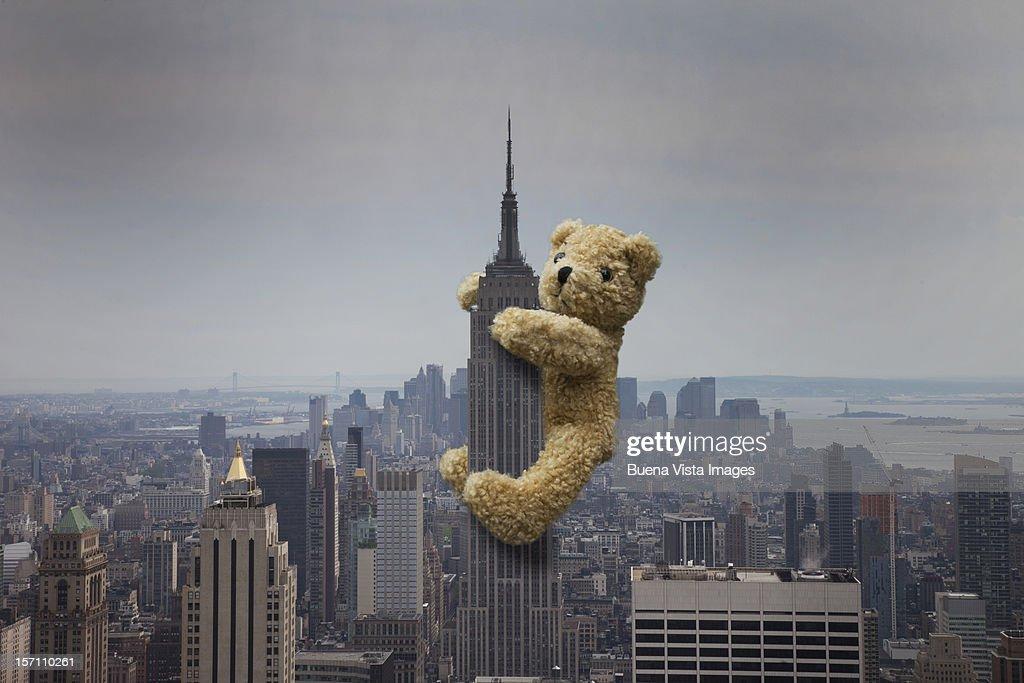 a teddy bear climbing the empire state building stock