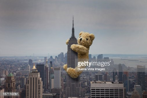 A teddy bear climbing the Empire State building