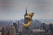 A teddy bear climbing the Empire State building