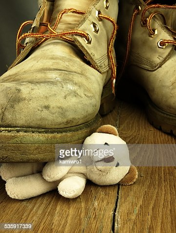 Teddy bear crushed by a heavy, old military boot. : Stock Photo