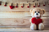 Teddy bear holding a heart-shaped pillow