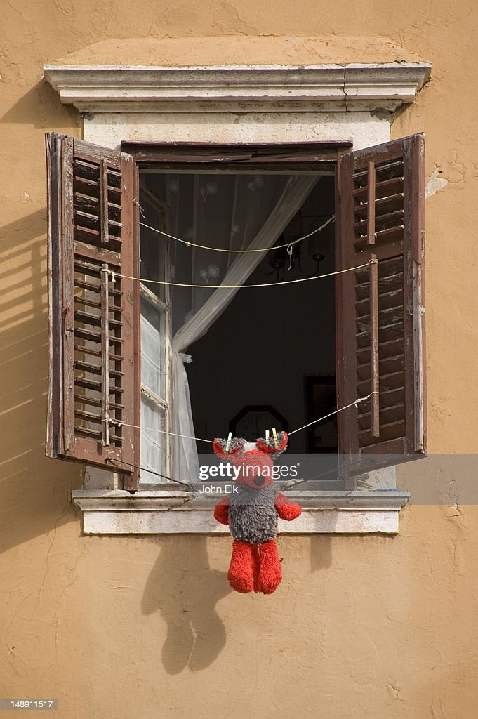Teddy bear hung out to dry on laundry line in window. : Stock Photo