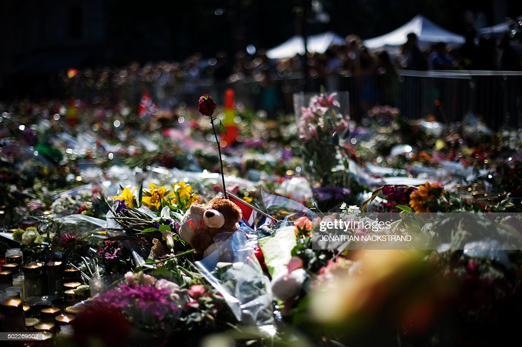 A teddy bear is left amongst flowers and candles at a makeshift memorial outside the Cathedral in Oslo in honor of the 76 victims of the July 22 twin...