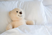 Cute white teddy bear in kids room. Teddy bear leaning on pillow in the child bed. A cute teddy bear lying in bed under the sheets.