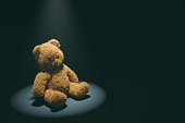 Teddy bear with torn eye illuminated by spotlight sits in dark room.