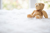 Teddy bear with a bow, on white fluffy blanket, by the window.
