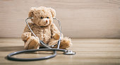 Teddy bear with a heart stethoscope sitting on a wooden background
