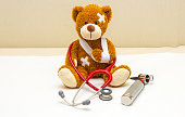Brown teddy bear with bandages and broken hand in pediatrician's office