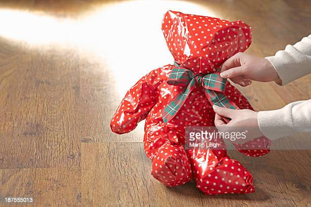 teddy bear wrapped in red christmas paper