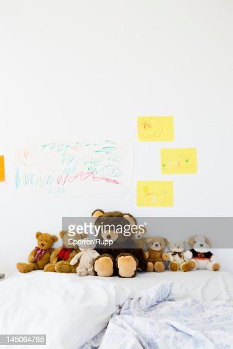Teddy bears and childs drawings on bed
