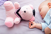 Teddy bear's eye was detached by toddler and in sleeping 10 months old baby hand, poorly attached button was removed by kid, beware of choking hazard for children concept, warning for parent