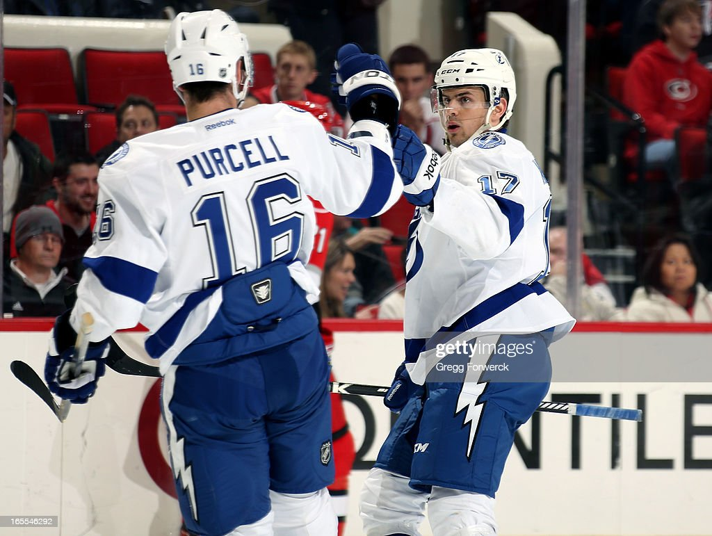 Teddy Purcell #16 and Alex Killorn #17 of the Tampa Bay Lightning celebrate a goal scored by teammate Tom Pyatt against the Carolina Hurricanes during their NHL game at PNC Arena on April 4, 2013 in Raleigh, North Carolina.