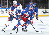 Teddy Purcell of the Edmonton Oilers skates with the puck against Tanner Glass of the New York Rangers at Madison Square Garden on November 9 2014 in...