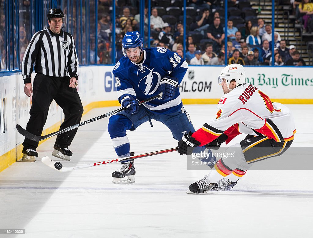 <a gi-track='captionPersonalityLinkClicked' href=/galleries/search?phrase=Teddy+Purcell&family=editorial&specificpeople=4537302 ng-click='$event.stopPropagation()'>Teddy Purcell</a> #16 of the Tampa Bay Lightning chips the puck by <a gi-track='captionPersonalityLinkClicked' href=/galleries/search?phrase=Kris+Russell&family=editorial&specificpeople=879805 ng-click='$event.stopPropagation()'>Kris Russell</a> #4 of the Calgary Flames during the third period at the Tampa Bay Times Forum on April 3, 2014 in Tampa, Florida.
