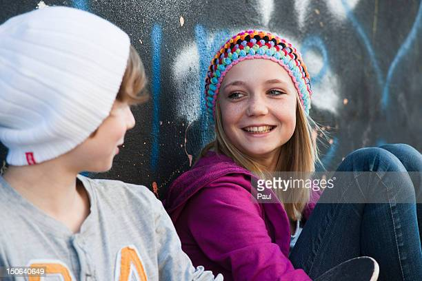 Teeange girl and boy sitting at graffiti wall