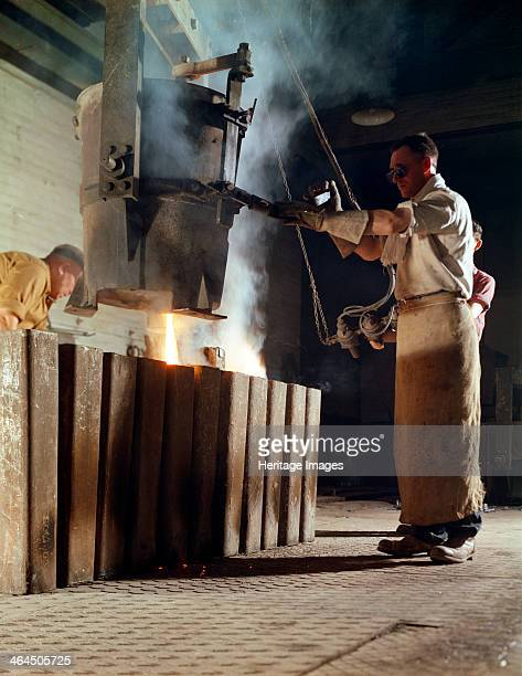 Teeming iron into ingots J Beardshaw Sons Sheffield South Yorkshire 1963 A steelworker in the process of teeming molten iron into ingots